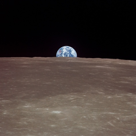 This image from Apollo 11 shows the Earth rising over the limb of the Moon much as the Harvest Moon does from our planetary perspective. Over the stark, scarred surface of the moon, the Earth floats in the void of space, a watery jewel swathed in ribbons of clouds.